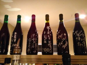Japanese clients sign bottles of Nouveau at Café de la Nouvelle Mairie